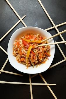 Macarrão de vista superior com legumes em um prato e pauzinhos