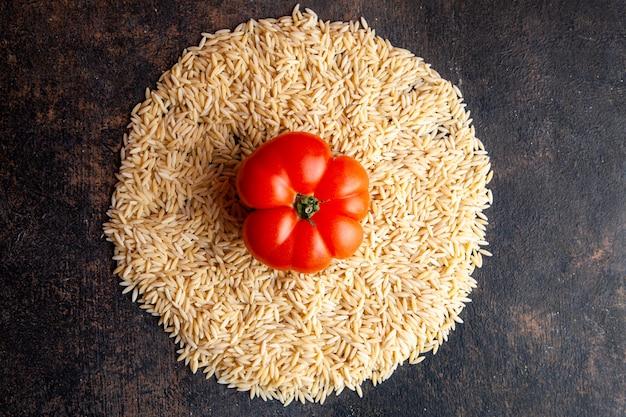 Macarrão de vista superior em forma de círculo com tomate neles no plano de fundo texturizado escuro. horizontal