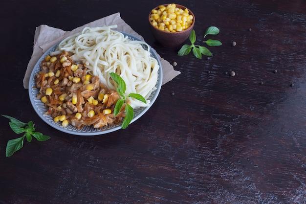 Macarrão delicioso com legumes em um prato grande. grãos de milho no banco.