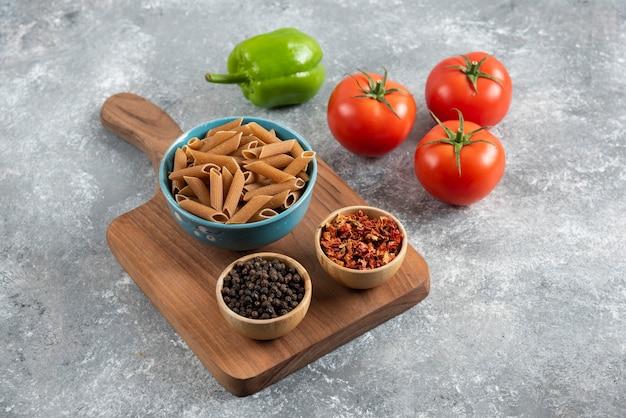 Macarrão dietético marrom na placa de madeira com vegetais e especiarias.