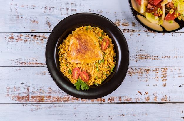 Macarrão e arroz com frango e legumes em uma tigela preta.