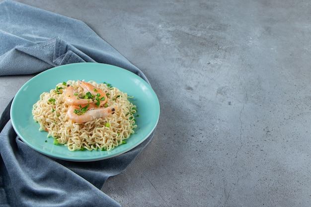Macarrão e camarão em um prato sobre um pedaço de tecido, no fundo de mármore.