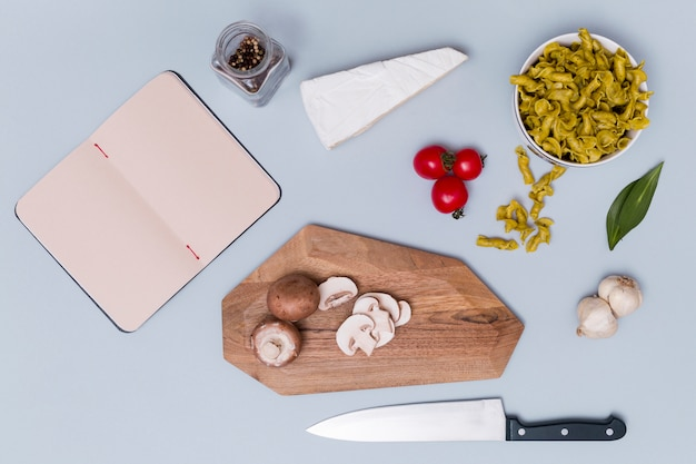 Macarrão e é ingrediente com diário em branco aberto no fundo liso