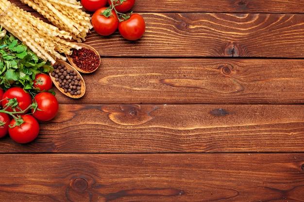 Macarrão e ingredientes em fundo de madeira com espaço de cópia. vista do topo.