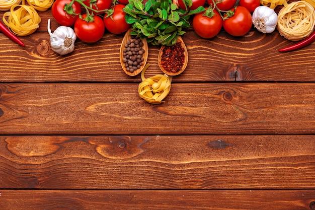Macarrão e ingredientes na mesa de madeira com cópia espaço plano de fundo. vista do topo.