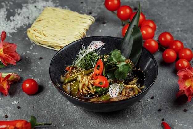 Macarrão e legumes refogados, em uma tigela preta