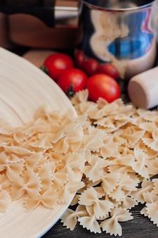 Macarrão e tomate em uma mesa de madeira