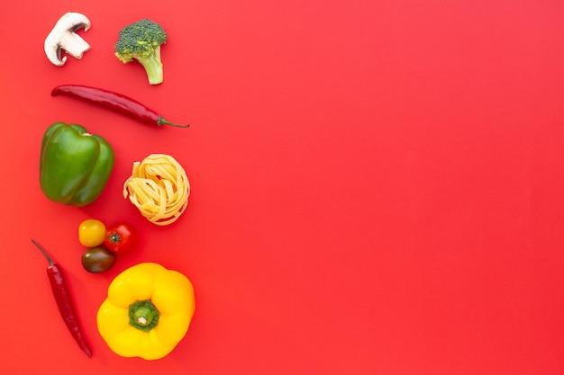 Macarrão e vegetais crus de tagliatelle em fundo vermelho vista superior copie a receita culinária do espaço