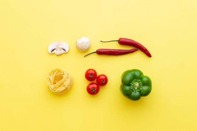 Macarrão e vegetais crus de tagliatelle em vista superior do fundo amarelo
