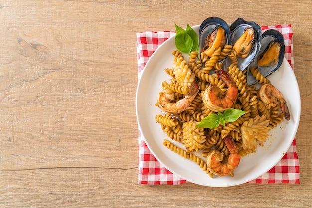 Macarrão em espiral frito com frutos do mar e molho de manjericão - estilo de comida de fusão