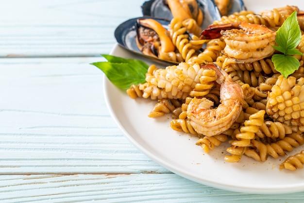 Macarrão em espiral frito com frutos do mar e molho de manjericão. estilo de comida de fusão