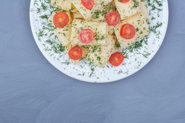 Macarrão em travessa branca com tomate cereja e ervas