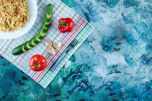 Macarrão em um prato ao lado de vários vegetais e garfo em uma toalha de chá, na mesa azul.
