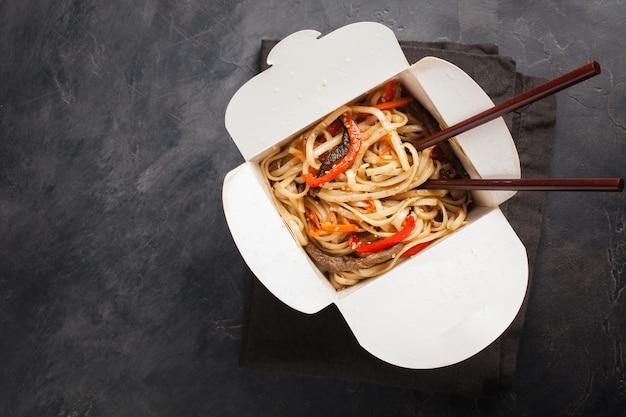 Macarrão em uma caixa com legumes e carne.