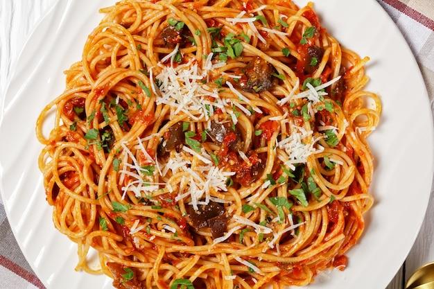 Macarrão espaguete alla norma em um prato branco em uma mesa de madeira texturizada branca, cozinha italiana, visão horizontal de cima, plano plano, macro