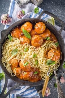 Macarrão espaguete caseiro com almôndegas em molho de tomate, fundo escuro de concreto acima