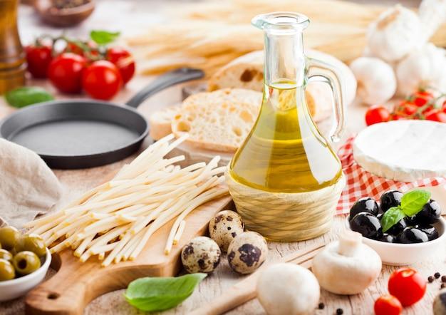 Macarrão espaguete caseiro com ovos de codorna com garrafa de azeite e queijo. comida italiana clássica da vila. alho, azeitonas pretas e verdes, azeite e pão.