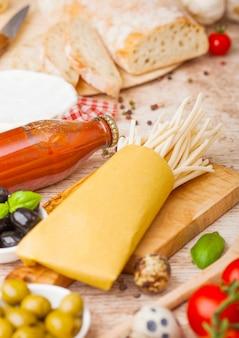 Macarrão espaguete caseiro com ovos de codorna com garrafa de molho de tomate e queijo na mesa de madeira. comida italiana clássica da vila. alho, champignon, azeitona preta e verde, pão e espátula.