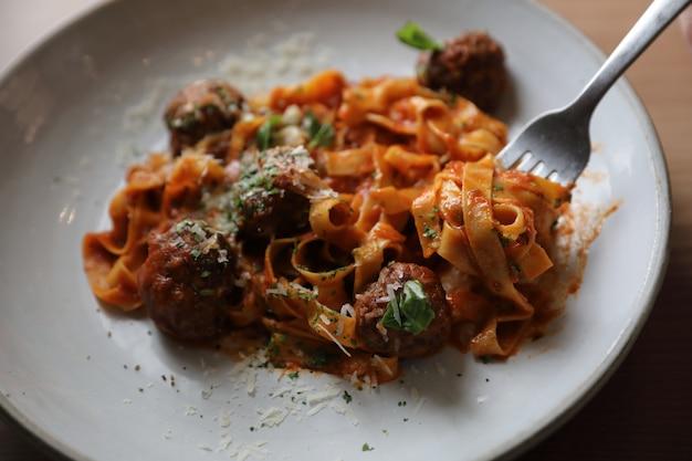 Macarrão espaguete com almôndegas de carne e molho de tomate no fundo de madeira