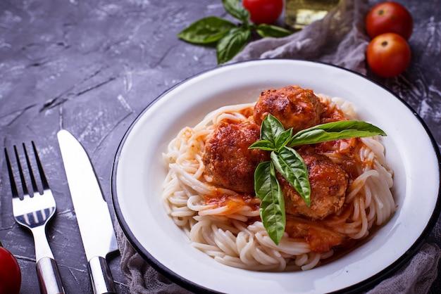 Macarrão espaguete com almôndegas e molho de tomate.