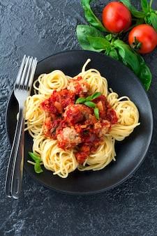 Macarrão espaguete com almôndegas, molho de tomate e manjericão em superfície escura