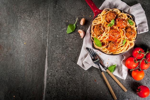 Macarrão espaguete com almôndegas, molho de tomate manjericão na panela de ferro fundido vermelho, na mesa de pedra preta
