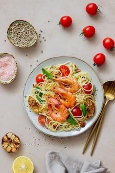 Macarrão espaguete com camarão, tomate, alho, espinafre e limão. cozinha italiana. frutos do mar. dieta.