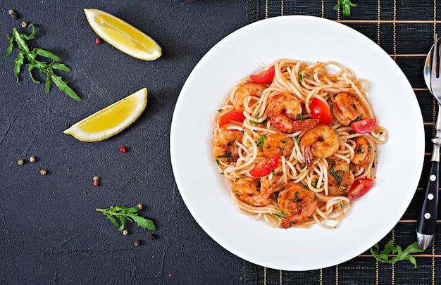 Macarrão espaguete com camarão, tomate e salsa. refeição saudável. comida italiana. vista do topo. configuração plana