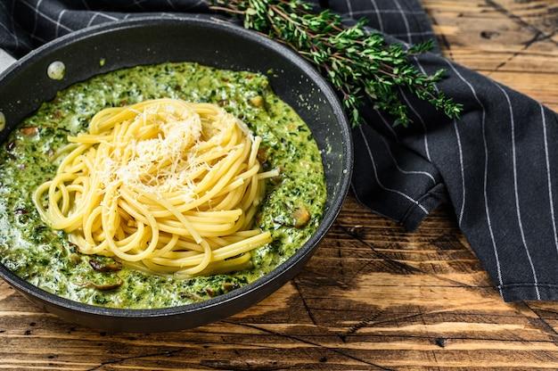 Macarrão espaguete com espinafre em molho de natas com parmesão em uma panela. fundo de madeira. vista do topo. copie o espaço.
