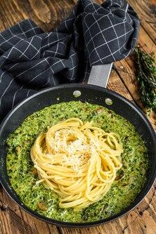 Macarrão espaguete com espinafre em molho de natas com parmesão em uma panela. fundo de madeira. vista do topo.