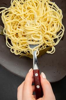 Macarrão espaguete com folhas de louro no garfo de prato em mãos femininas sobre fundo preto.