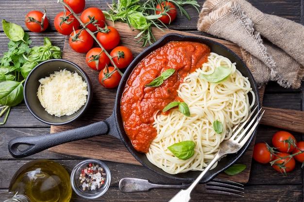 Macarrão espaguete com molho de tomate e manjericão sobre madeira