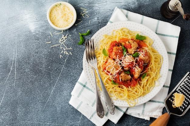 Macarrão espaguete com molho de tomate, queijo parmesão, manjericão e almôndegas em placa de cerâmica branca sobre fundo cinza de concreto ou pedra