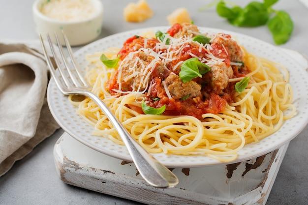 Macarrão espaguete com molho de tomate, queijo parmesão, manjericão e almôndegas em um prato de cerâmica branca na superfície de concreto cinza