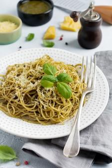 Macarrão espaguete com molho pesto, manjericão e queijo parmesão em uma placa de cerâmica branca e concreto cinza ou fundo de pedra. prato tradicional italiano.