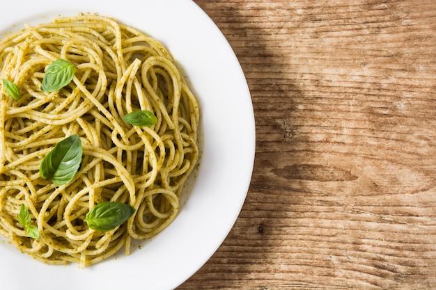 Macarrão espaguete com molho pesto no espaço da cópia de mesa de madeira