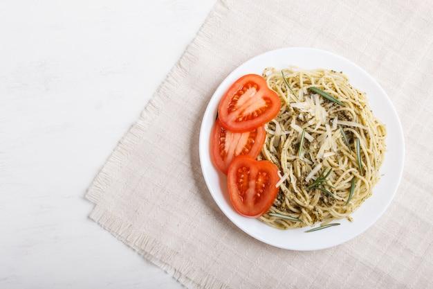 Macarrão espaguete com molho pesto, tomate e queijo numa toalha de mesa de linho