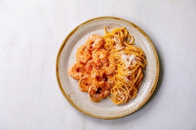 Macarrão espaguete com tomate com camarão camarão ao molho e queijo parmesão servido em prato de cerâmica manchado sobre parede de mármore branco. configuração plana, copie o espaço