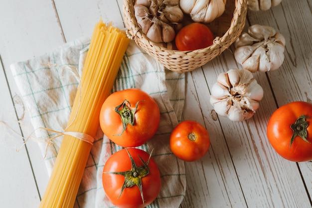 Macarrão espaguete com tomate e alho em superfície de madeira branca