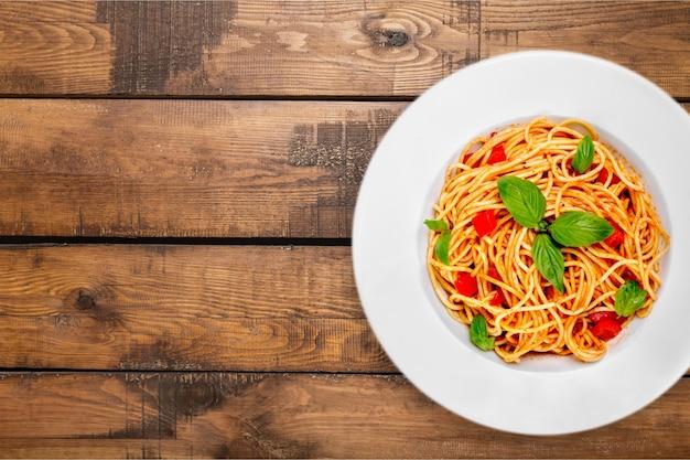 Macarrão espaguete com tomate e salsa na mesa.
