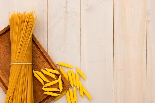 Macarrão espaguete cru e macarrão penne com placa de corte na mesa de madeira