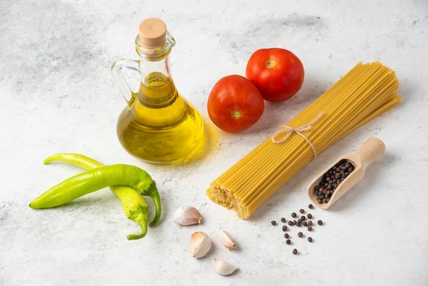 Macarrão espaguete cru, garrafa de azeite, grãos de pimenta e vegetais na mesa branca.