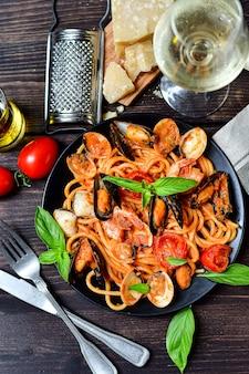 Macarrão espaguete de frutos do mar com amêijoas e camarões com mexilhões e tomates em um prato branco com uma mesa de madeira. receita da culinária italiana. vista do topo