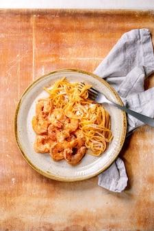 Macarrão espaguete de tomate com camarões camarões ao molho e queijo parmesão servido em prato de cerâmica manchado com garfo e guardanapo de pano sobre a parede de pedra marrom. configuração plana, copie o espaço
