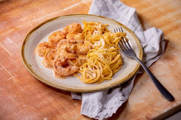 Macarrão espaguete de tomate com camarões camarões ao molho e queijo parmesão servido em prato de cerâmica manchado com garfo e guardanapo de pano sobre a parede de pedra marrom.