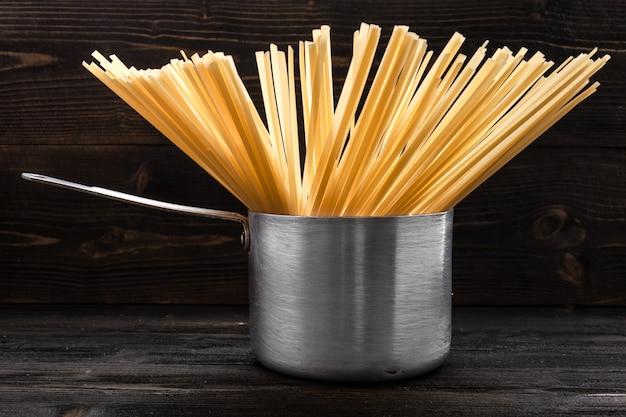 Macarrão espaguete em uma panela de alumínio retrô com uma alça na mesa de madeira escura