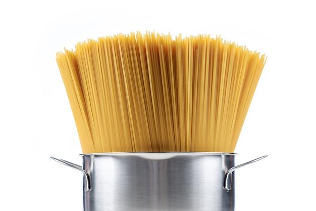 Macarrão espaguete em uma panela em um branco