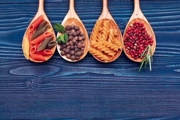Macarrão espaguete, legumes e especiarias, na mesa de madeira