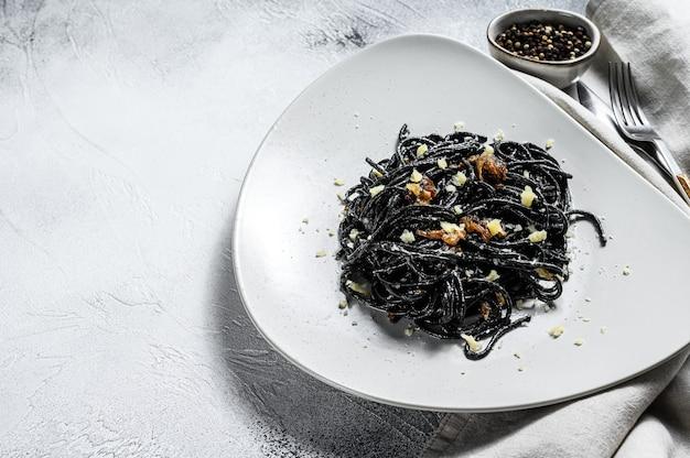 Macarrão espaguete preto com atum em molho de natas. plano de fundo cinza. vista do topo. copie o espaço.