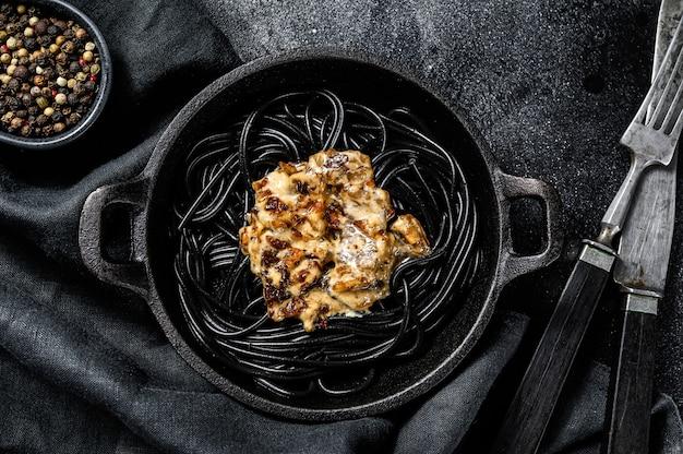Macarrão espaguete preto com salmão em molho de creme. fundo preto. vista do topo.